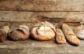 Different fresh bread, on old wooden table — Stock Photo