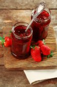 Jars of strawberry jam with berries on wooden background — Stockfoto