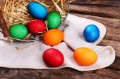 Easter eggs in basket on vintage wooden planks background — Stock Photo