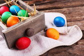 Easter eggs in box on vintage wooden planks background — Stock Photo
