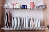 Clean dishes drying on metal dish rack on shelf — Stock Photo