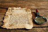 Grunge paper with hieroglyphics with magnifier on wooden background — Stok fotoğraf