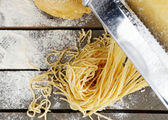 Making vermicelli with pasta machine on wooden table with flour, top view — Stock Photo