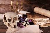 Still life with human skull, retro book and candlelight on wooden table, closeup — Stock Photo