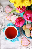 Composition of spring flowers, tea and cookies on table close-up — Stock Photo