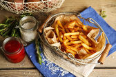 Tasty french fries and fresh potatoes in metal baskets on wooden table background — Stockfoto