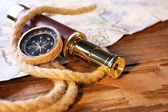 Marine still life spyglass, compass, rope and world map on wooden background — Photo