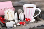 Heart shaped teabag tags, box and cup of tea on wooden background — Стоковое фото