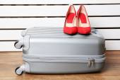 Gray suitcase with female shoes on floor on white planks background — Stock Photo