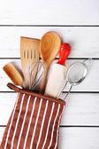 Set of kitchen utensils in mitten on wooden background — Stock Photo