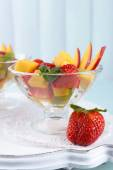 Fruit salad with mint in glassware on wooden table and planks background — Stockfoto