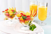 Fruit salad with mint and orange juice in glassware on wooden table and planks background — Stockfoto