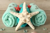 Beautiful towels with sea stars and decorative stones on wooden background — 图库照片