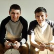 Two handsome young men playing video games in room — Stock Photo #67460899