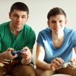 Two handsome young men playing video games in room — Stock Photo #67460903