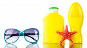 Bottles of suntan cream with sunglasses and sea star isolated on white — Stockfoto
