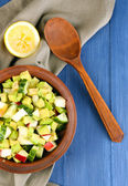 Salad with apple and avocado in bowl with napkin on wooden background — Stock Photo