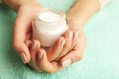 Female hands with jar of cream on fabric background — Stock Photo