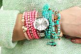 Stylish bracelets and clock on female hand close-up — Stockfoto
