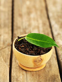 Black tea with leaf in bowl on old wooden table — Stock Photo