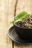 Green tea with leaf in cup on old wooden table — Stock Photo