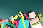 Bright school supplies on blackboard background — Stock Photo