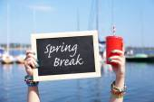 Spring break concept. Chalkboard in female hands on beach background — Stock Photo