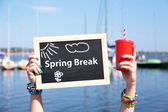 Spring break concept. Chalkboard in female hands on beach background — Stock Photo