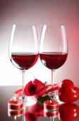 Composition with red wine in glasses, red rose and decorative heart on colorful background — Stock Photo