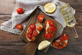 Slices of white toasted bread with canned tomatoes and lime on cutting board on wooden table background — Stock Photo