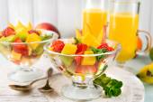 Fruit salad with mint and orange juice in glassware on wooden table and planks background — Stock Photo