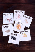 Different seeds on pieces of paper on wooden background — Stock Photo