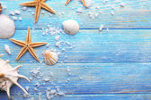 Sea stars and shells on wooden background — Stock Photo