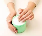 Female hands holding jar of cream isolated on white — Stock Photo
