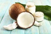 Fresh coconut oil in glassware and green leaf on color wooden table background — Photo
