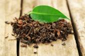 Black tea with leaf on old wooden table — Stock Photo