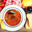 Tasty soup with mussels, tomatoes and black olives in bowl on wooden background — Stock Photo #68104809