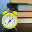Stack of books with alarm clock on wooden desk and colorful background — Stock Photo #68105183