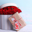 Bouquet of red roses in textile box with present on wooden background — Stock Photo #68109107