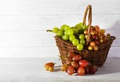 Grapes in basket on wooden background — Stock Photo