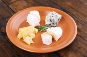 Slices of different sort of cheese on plate on wooden table background — Fotografia Stock