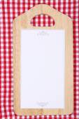 Cutting board with menu sheet of paper on squared fabric background — Stock Photo
