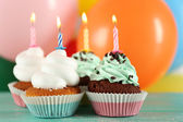Delicious birthday cupcakes on table on bright background — Stock Photo