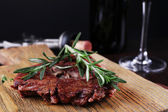 Grilled steak with bottle of wine on dark background — Stock Photo