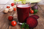 Glass of beet juice with vegetables on wooden table close up — Stock Photo