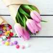 Beautiful pink tulips in paper with sweets on wooden background — Stock Photo #68110589