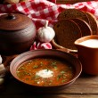 Ukrainian beetroot soup - borscht in bowl and pot, on napkin, on wooden background — Stock Photo #68110861