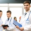 Attractive male doctor with team in conference room — Stock Photo #68114027