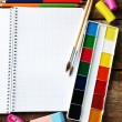 Notebook and bright school stationery on old wooden table — Stock Photo #68117099