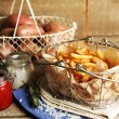 Tasty french fries and fresh potatoes in metal baskets on wooden table background — Stock Photo #68118277